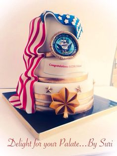 a cake for promotion in the Navy, 3 tiers cake with different flavors ! Pistachio, Red Velvet and Vanilla. The American Flag was made with Fondant and the images was all edible .All the details was hand painted gold color .