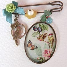 Broches de bronce con medallas de diferentes pájaros.