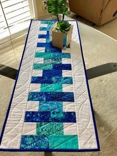 Dies ist eine schöne handgemachte, reversibel, gesteppte Tischläufer, der 15 1/2 x 38 1/2 misst. Das Oberteil verfügt über 100 % Baumwolle in verschiedenen Schattierungen von blau und Türkis und weiß. Das weiß ist kleinen weißen Punkten auf weißem Hintergrund (weiß auf weiß). Die