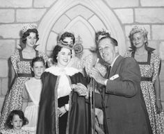 "vintagethemeparks:""Shirley Temple told the story of Sleeping Beauty during the official opening of the interior of the Castle at Disneyland Sunday, April 28. Left to right: Daughter, Lori, three; daughter, Susan, nine; Ms. Temple and Walt Disney Disneyland ladies in waiting stand by to escort them through the castle interior. Photograph dated April 29, 1957."" LA Public Library Images"