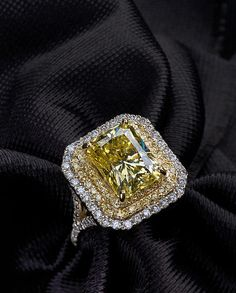 Canary yellow diamond ring surrounded with white diamonds.