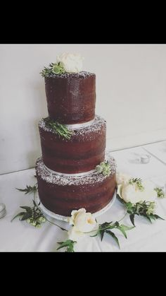 Chocolate wedding naked cake semi naked brownie layers three tiers melted mars bar between layers chocolate icing thin white flower decoration homemade silver cake board dowel supports