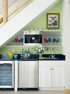 Use the space under stairs. Combine small-scale appliances and a sink along the floor and extend simple shelves in the upper areas. Install recessed lighting on the slanted ceiling in order to make the most of the low ceiling.