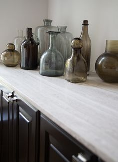 A collection of glass vases and bottles makes for interesting decor on a cabinet countertop. Decorating Your Home, Interior Decorating, Interior Styling, Interior Design, Home Renovation, Home Remodeling, Travertine Countertops, Painted Ceramic Plates, Fireplace Wall