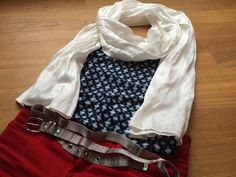 Creamy bamboo scarf, blue sleeveless top, red jeans and a belt made of metal.