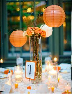 Arrangements of orange and yellow circus and spray roses decorated the reception tables and matched the bridal bouquet. Orange and ivory lanterns with LED lights hung from curly willow branches and added a warm glow to the centerpieces.  (White flowers with green/blue lanterns?)