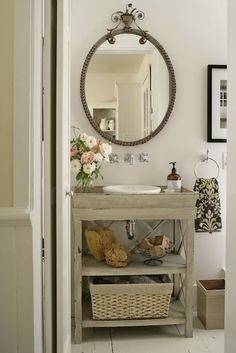 Vintage bathroom with gray washed wood single bathroom vanity, polished nickel wall-mount faucet kit, vintage oval mirror, ivory & black damask towel and plank floors.