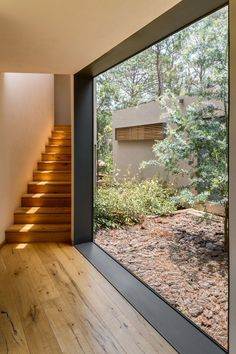 A large floor-to-ceiling window with thick black frames lets plenty of natural light into the home, and views of the trees add to the feeling of being in a forest.