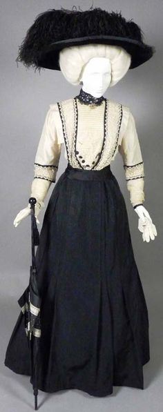 1907-1908 black silk faille and cream silk afternoon dress with net and lace trim. From 1907-1911, dresses with short sleeves over fitted, sheer, pleated ones, with sheer fabric at the neck, were all the rage. Enormous hats were popular until about 1912.