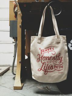 "American Apparel tote with ""Travel Honestly Down Life's Path"" screen printed in red ink by the awesome Ben Poole. Carry this tote with you to farmer's market or your next jet-setting adventure. Specs: 100% Bull Denim Woven Cotton construction Dimensions: 14 3/8"" x 14"" (36.5cm x 35.6cm) Dual handles"