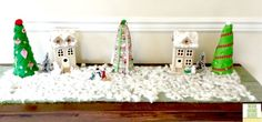DIY Christmas village with wooden craft houses. DIY Christmas trees made with felt and syrofoam cones.