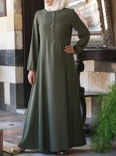 Sweet, soft, and practical, this feminine dress can also double as an abaya. Well-placed pintucks grace the front, while the sleeves boast a slight flare. With a wide cut hem at the bottom, you will walk with a royal grace and flow. It is a made from a delicate modal fabric finished with a soft peach teach.