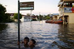Children joke in a street flooded by the rising Rio Solimoes, one of the two main branches of the Amazon River, in Anama, Amazonas state, Brazil June 3, 2015. REUTERS/Bruno Kelly
