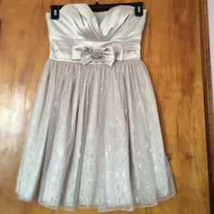 Beautiful Strapless Cream Dress Strapless Cream dress with satin like top and and double bow with silver pendant on it. Bottom of it flares out slightly and has sequins scattered about it. Very cute for fancy occasions and no signs of wear. Make me an offer! Trixxi Dresses Strapless