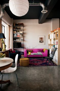 Modern room decor - white dining chars, hot pink sofa, pink toned oriental rug, black and blue chairs, minimal metal bookshelf, concrete floors, white lantern, birch IKEA shelves