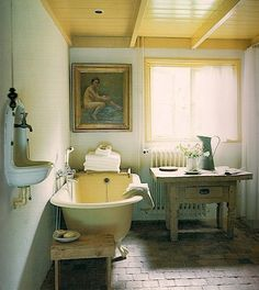 Love this rustic old world elegant bathroom with clawfoot tub, bidet, and painting.