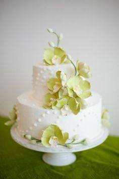 Branches of bright green cymbidium orchids dance around this two-tier cake covered in local NYC honey buttercream. By Sugar Flower Cake Shop.