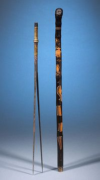 Spearfishing Cane: A magnificently carved fish and serpent motif is carved into the shaft of this spearfishing cane. The double-bladed spear concealed within the shaft can be attached to the base of the cane, allowing for greater pole length and leverage when hunting.