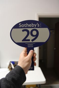 """""""Sothebys"""" shape paddle, 3mm Blue Sintra PVC.  Full-color graphic logo digitally printed.  An example of printing white ink to rigid substrate.  Printing white or a color ink on top of white ink costs more, fyi.  Sometimes its easier if you start out with white plastic and floodcoat your color to get a similar effect.  Only real difference is you'd see the white edges of the plastic.  Here you'd see blue everywhere since the plastic is a solid blue to begin with."""