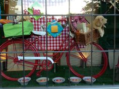 A red bike provides a focal point for this window filled with picnic baskets and summer fun items. Display by Leslie Janus, Orange Tree Imports, Madison, WI Spring Window Display, Window Display Retail, Retail Windows, Shop Windows, Pet Store Display, Store Displays, Diy Projects Etsy, Animal Room, Diy Stuffed Animals