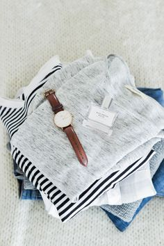 pile of clothes for capsule wardrobe, gray madewell shirt, daniel wellington watch, urban outfitters perfume