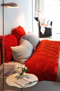 This white bedroom features a bed with vibrant red and light gray bed linens plus modern bedside lights on each side. A black armchair sits in the corner of the room, providing the perfect space for relaxing.