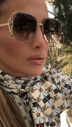 df06bfa4c20 Jennifer Lopez pairs a Gucci silk shirt with web kisses print with  sunglasses by Elie Saab