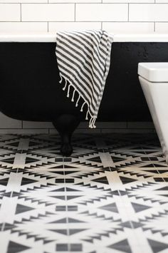 Hip black and white bathroom with linear subway tiled walls accented with black grout framing the black claw foot tub draped with a Fouta towel atop Tulum floor tile from the Cement Tile Shop.