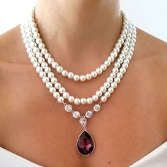 Three strand Swarovski pearl necklace and the highlight is a large amethyst color Swarovski pendant hanging from clear cubic zirconia links. #purplewedding  Don't forget to follow our group: @