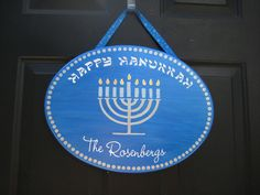 """Shimmer Blue """"Happy Hanukkah"""" door plaque.Sparkling flames on the candles. Ribbon has Stars of David on it. Personalized with your family's name in vinyl. Oval plaque with handpainted menorah measures 16""""L by 12""""H.    Please include the last name for the plaque in the paypal notes."""
