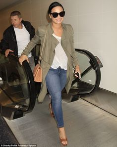 Jet set style: Demi Lovato added neutral accessories to her classic combination of jeans a...