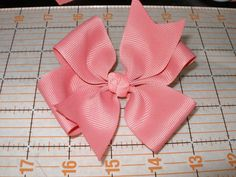 Put a tiny dot of glue on the center of your bow and secure the knot in the center. Then fold each tail over one at a time securing it with hot glue o...