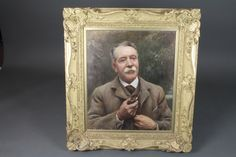 """Lance Calkin, British 1859-1936, oil on canvas, an early 20th Century head and shoulder portrait of a gentleman, wearing a  tweed sports jacket and waistcoat with pipe, signed and dated 1913 24.75""""h x 21""""w, within a foliate carved giltwood frame, frame 35""""h x 32.5""""w"""