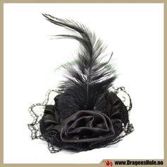 En liten pyntehatt laget i svart fil. Festes til hodet med den fastlimte klypen som følger med. Mål: Diameter ca 7cm, høyde ca 3,5cm, pluss blonder og fjær.