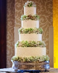 Turning Stone Wedding Cake - Four Tiered Cake Separated and Topped with Fresh Hydrangea.  Subtle Champagne Shimmer Spray Over White Fondant - Top Tier has Piped Monogram and Bottom Tier has Edible Pearls.