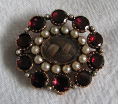 "c. 1870 Mourning brooch This pin is set with garnets and pearls. The hair is plaited and secured under glass. On the back of one of the settings for the garnet is a tiny inscription that just says ""Edward""."