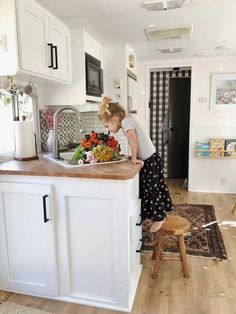 The countertop is a repurposed IKEA desktop cut to size. Tagged: Kitchen, White Cabinet, Wood Counter, Rug Floor, Refrigerator, Medium Hardwood Floor, Recessed Lighting, Drop In Sink, Microwave, and Ceramic Tile Backsplashe.