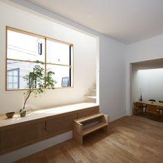 Wooden stairs climb up through a narrow lightwell inside this house by Japanese…