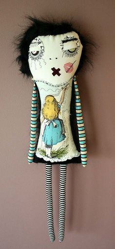 Oh My....I don't quite know what to say.  Is that a line struck through the kiss lips.....Poor thing. Is she recovering from a little nip and tuck on the eyes?  Love the fussy cut Alice in Wonderland fabric.  She needs someone to love her.