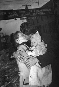 A US soldier is welcomed home by his wife and baby, 1940s.