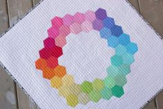 """Megan Bohr from Canoe Ridge Creations used Robert Kaufman Fabrics to make this colorful and happy English paper pieced hexagon mini quilt.  """"I straight-line quilted this mini quilt rather than distract from the over all design with more intricate quilting -- plus, it's my favorite way to quilt! I used #Aurifil Threads (color 2024, 50 wt.) and my Bernina walking foot to create these straight-line quilting lines about 1/2"""" apart. The resulting texture just makes me happy! """""""