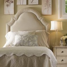 Upholstered headboard with more padding to emphasize the border, with flat tape and nailheads.