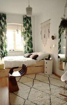tapis blanc noir, chambre à coucher design cocooning, rideaux longs verts, lit en bois clair et parquet