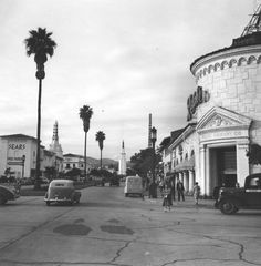 """Westwood Village by Ansel Adams  Intersection of Lindbrook Drive (right) where it meets Westwood Boulevard (foreground) just outside of a Ralph's supermarket in Westwood Village. Designed by architect Russell Collins and built in 1929, the market is identified by the words """"Ralphs Grocery Co.,"""" seen over the doorway. Various businesses, including Sears and the Fox Westwood theater, are visible in the background,"""