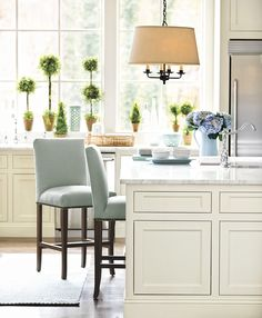 A large white kitchen island is perfect for family meals, or even homework, when helped by a few comfortable bar stools