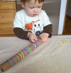 Craftulate: Cardboard Tube and Elastic Hair Bands make an easy DIY fine motor activity. Visit pinterest.com/arktherapeutic for more #finemotor ideas