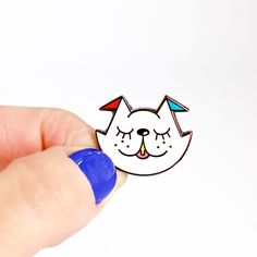Is it a cat? Is it a dog? Whatever you want it to be! Super cute pin by Chris Uphues. Approx. 1-inch. Enamel, black nickel, and rubber backing.