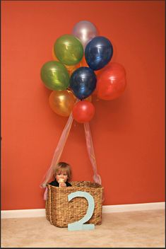 """Idea: Make your own """"Oh the Places You Will Go!"""" hot air balloon for photos. All you need is a basket, cardboard and wrapping paper for the age sign, ribbon and helium balloons!"""