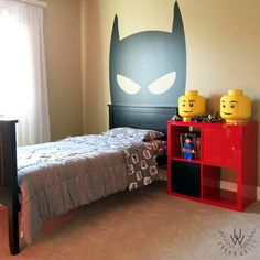 Large black superhero wall decal used as a headboard in a kids room. The room has a bed with red shelving and yellow lego toys beside it.