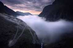 """""""The mountain road, Trollstigen, in western Norway. I was lucky enough to live here for two months during summer and one evening I saw the valley filling with fog, so I drove up the road to watch the late summer midnight sun set as the fog swayed through the valley below.""""  —photographer Sean Ensch"""